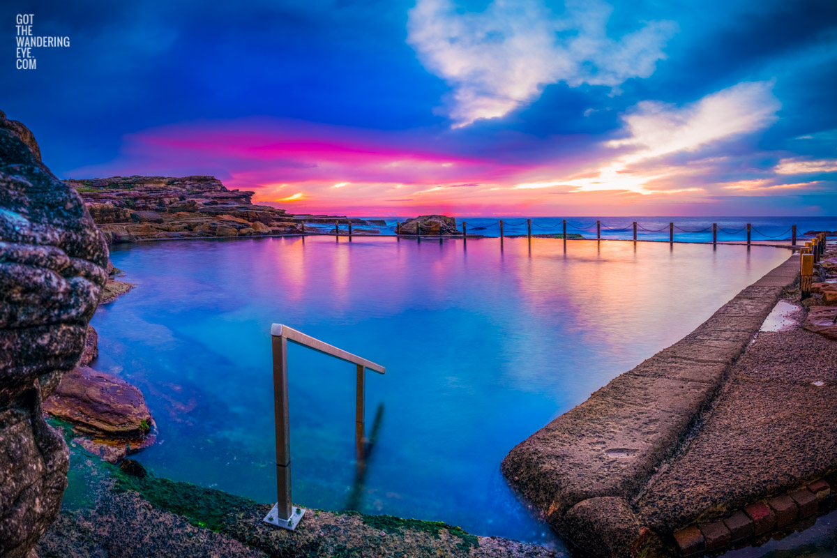 A pink sky cloudy sunrise over beautiful blue still waters and refections at an empty Mahon Pool, Maroubra.