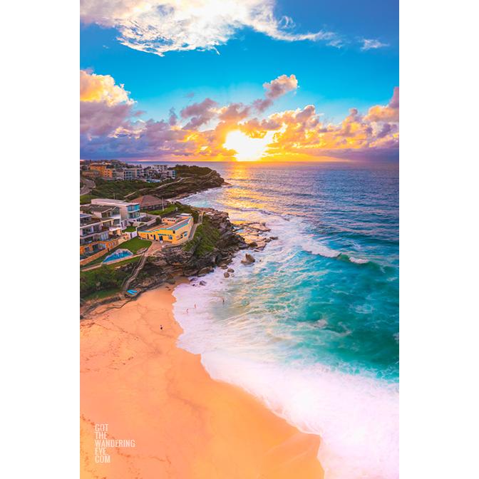 Golden sun rising over Tamarama Surf Life Saving Club, as swimmers enjoy a morning swim on an empty beach.