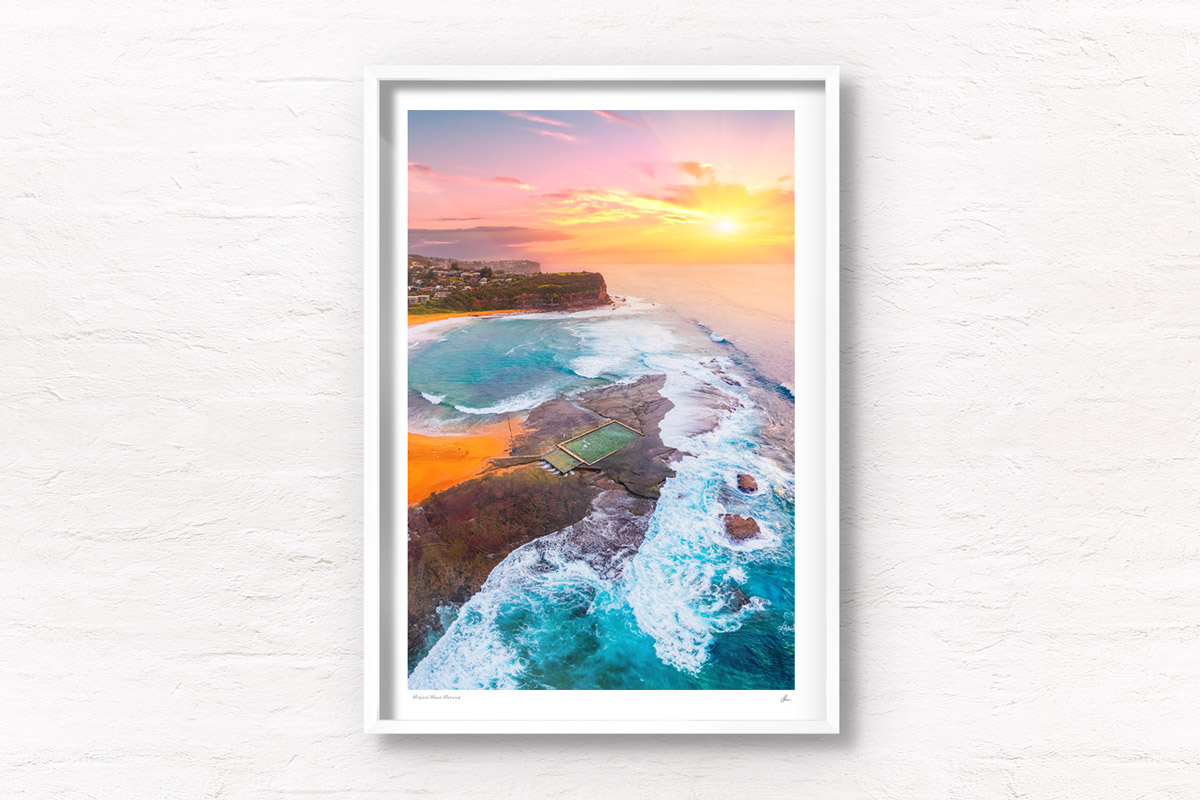 A morning sunrise peering through a cloudy sky, lighting up Mona Vale Rockpool in Sydneys Northern Beaches.