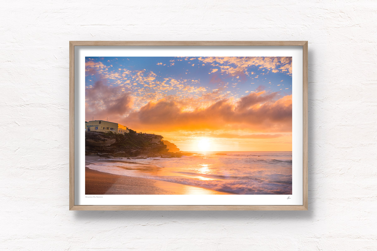 A glorious glowing sunrise through puffy clouds rising over Tamarama Beach